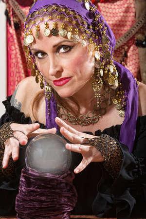 adivino: Señora bonita agitando las manos sobre la bola de cristal Foto de archivo