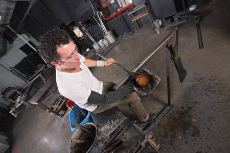 sculpting: Handsome glass artisan handling glowing hot object