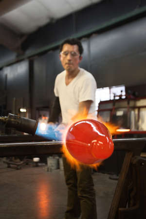 Glass factory worker forming glass object on flame