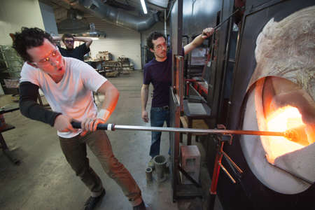 Glass craftsman placing art in hot blast furnace photo