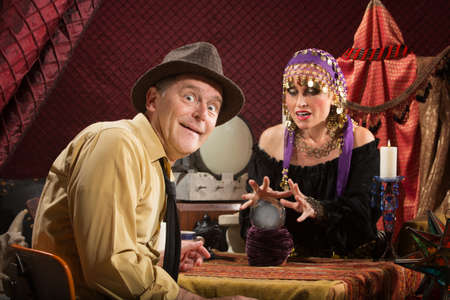 to curse: Smiling businessman getting his fortune from pretty gypsy woman