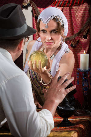 Fortune teller holding crystal ball in front of scared man photo
