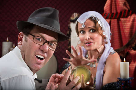 Unlucky sneering man with fortune teller and crystal ball  photo