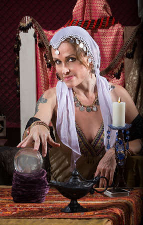 Exotic Romani woman with candle and crystal ball photo