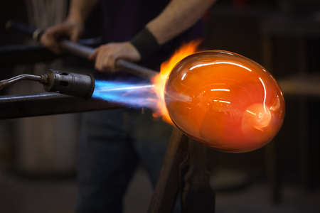 Blue and red flames on a hot glass vase Фото со стока