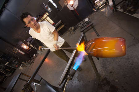 Glass factory worker holding vase near hot blowtorch photo