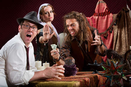 fortune teller: Insulted fortune teller with surprised customer indoors Stock Photo
