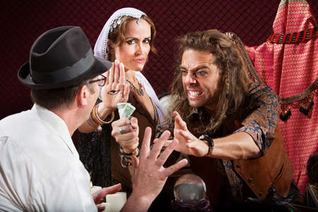 soothsayer: Aggressive fortune tellers taking money from man in hat Stock Photo