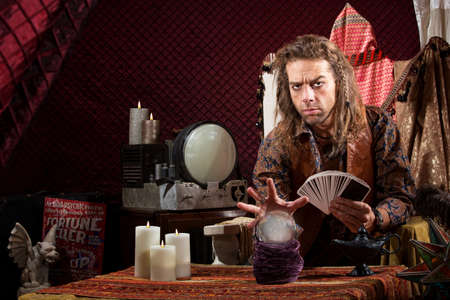 Male fortune teller with tarot cards waving hand over crystal ball Stock Photo - 20529781