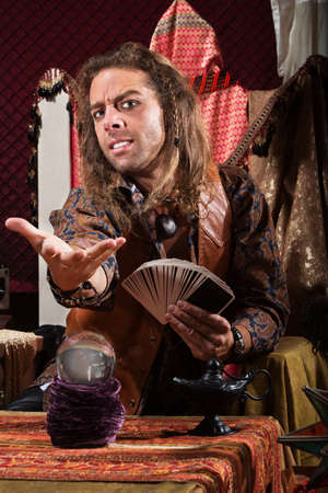 soothsayer: Handsome male fortune teller with tarot cards and crystal ball Stock Photo