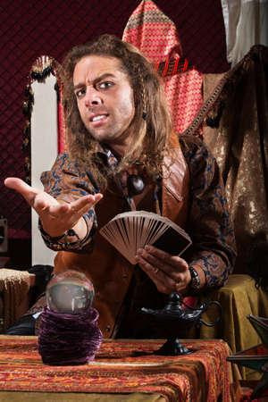 adivino: Hermoso adivino macho con las cartas del tarot y la bola de cristal