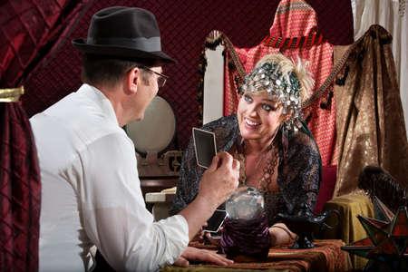 adivino: Riendo gitana rubia con el cliente holding del tarot Foto de archivo
