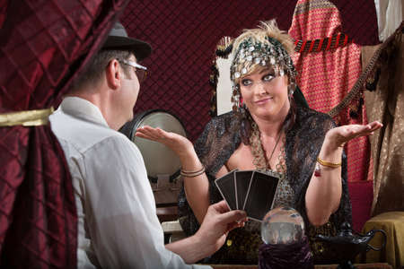 soothsayer: Customer showing happy tarot cards to fortune teller