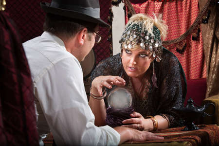 Pretty female fortune teller talking to customer over crystal ball