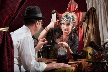 Fortune teller gesturing a gun to her head with customer Stock Photo - 20529787
