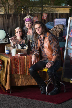 Handsome gypsy man sitting with female fortune tellers