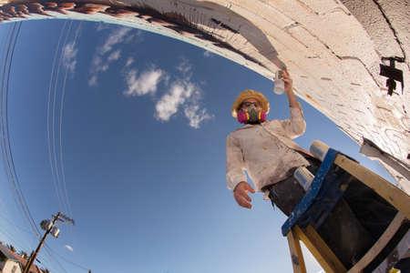 Grandangolo di dissimulata artista di graffiti a lavorare su murales