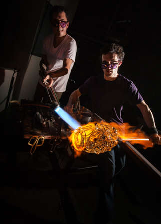 sculpting: Men working with flaming blowtorch on glass art piece