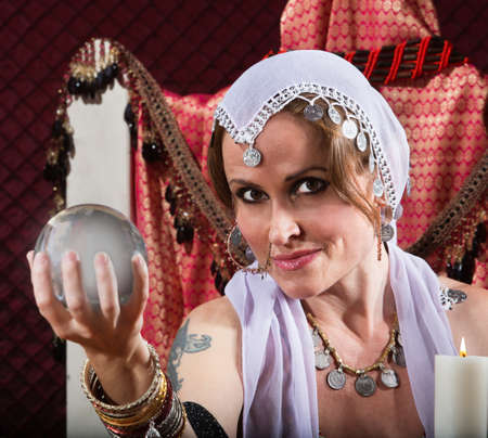 crystal gazing: Gorgeous female fortune teller holding a crystal ball