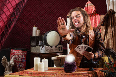 Soothsayer with clenched teeth holding the evil eye in his palm Stock Photo