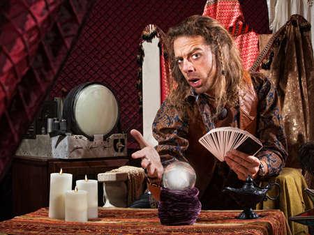 adivino: Atraer hombre con las cartas del tarot y la bola de cristal Foto de archivo