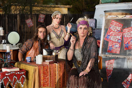 Trio of serious fortune tellers sitting outside with table Stock fotó