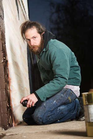 sitting on the ground: Bearded adult European graffiti artist kneeling on ground
