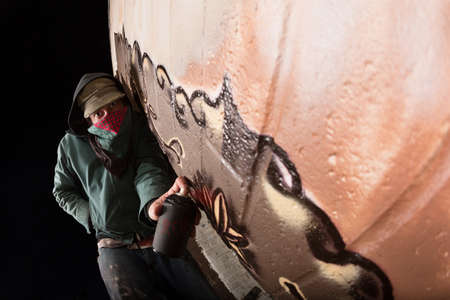 vandal: Hooded vandal spray painting on wall outdoors