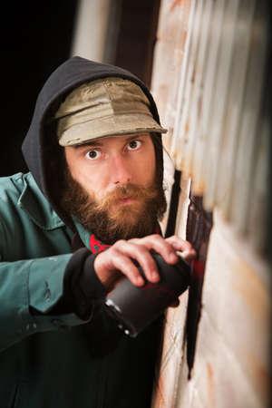 vandal: Sneaky vandal spray painting a wall outdoors