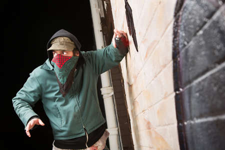 Scared disguised criminal defacing a wall outdoors