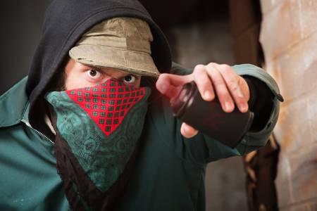 pandilleros: Miembro de una banda resistente con pintura en aerosol puede Foto de archivo