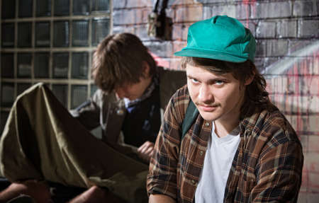 Frustrated young homeless man with friend sitting outside photo