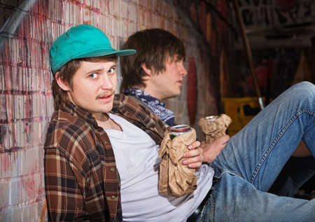 Two drunk young European men sitting outside
