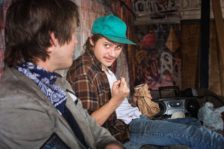Two homeless teenagers with brown paper bag talking Stock Photo