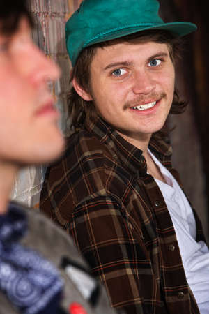 homeless man: Smiling teen looking over at friend while sitting Stock Photo