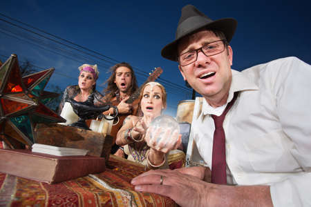 soothsayer: Distressed businessman sitting at a fortune teller table outside Stock Photo