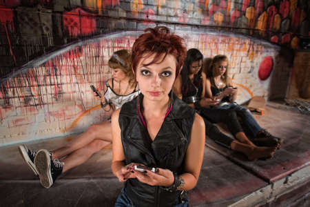 Serious young woman in leather top with smart phone photo