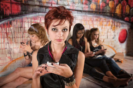 Group of pretty teenage girls using cell phones photo