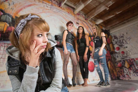 harassing: Insulted blond teenager looking over at group of girls