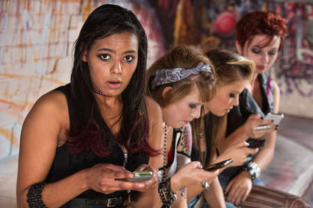 Worried Black teenager next to friends using phones photo