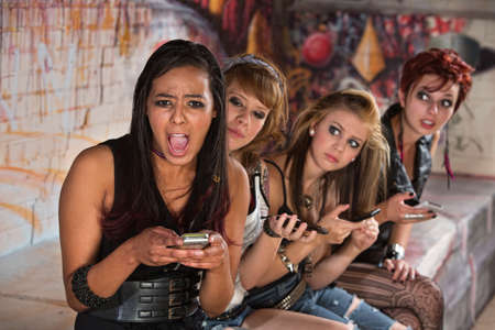 Insulted pretty young woman with friends on phones photo