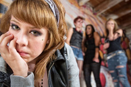 insulting: Sad European young woman being teased by group of teenagers Stock Photo