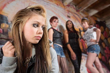 Mean group of people looking over at insecure teen