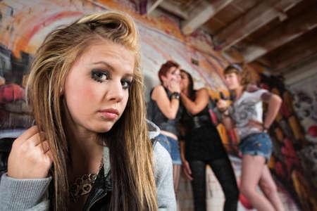 harassing: Group of people making fun of sad blond teenager