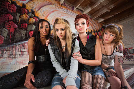 Sad group of young women sitting together in garage photo