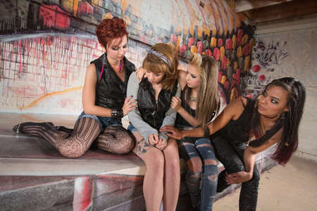 sitting down: Afraid young woman sitting with friends in urban setting Stock Photo