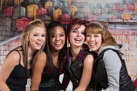 bff: Group of four cute diverse urban teenagers laughing