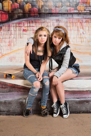 bff: Pair of cute young female skateboarders sitting together