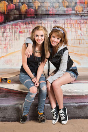 bff: Two smiling female skateboarders sitting together