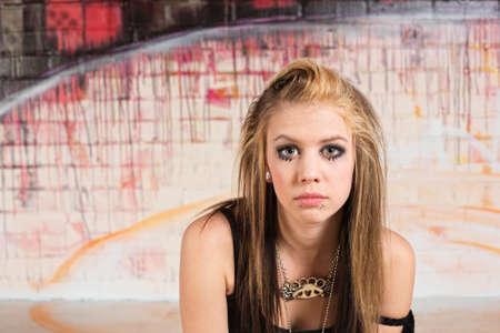 remorse: Pensive young white female teenager in urban scene